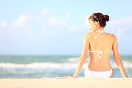 Beach holidays woman enjoying summer sun sitting in sand looking happy at copy space  Beautiful young bikini model  Mixed race Caucasian   Asian Chinese  photo
