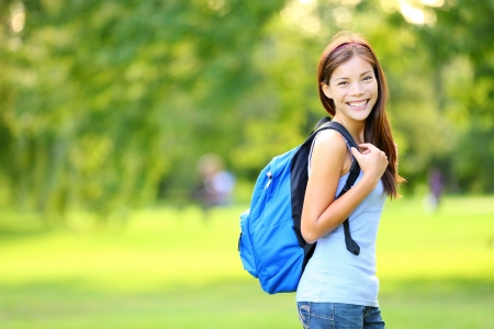 school campus: Girl student in summer   spring park standing with backpack or school bag smiling happy  Portrait of young Asian female university student - mixed race Asian Chinese   Caucasian woman