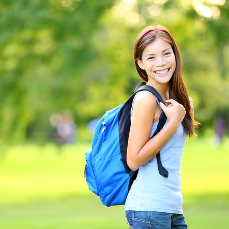 Student girl outside in summer park smiling happy  Asian female college or university student  Mixed race Asian   Caucasian young woman model wearing school bag  photo