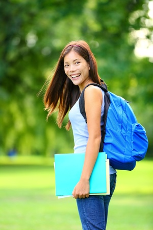 University   college student girl standing happy smiling with book or notebook in campus park  Beautiful young mixed race Asian   Caucasian young woman brunette  photo