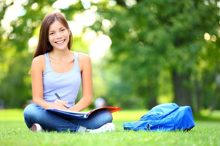 Student studying in park  Joyful happy asian girl student sitting writing and reading outside on university campus or park  Mixed race Chinese Asian   Caucasian female student woman looking at camera  photo