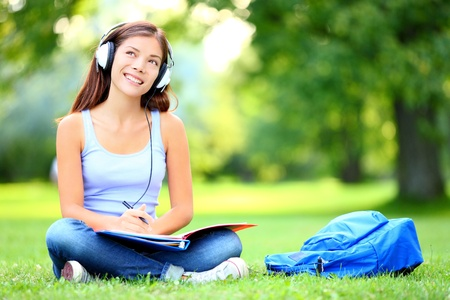 college: Female student girl outside in park listening to music on headphones while studying  Happy young university student of mixed Asian and Caucasian ethnicity  Stock Photo