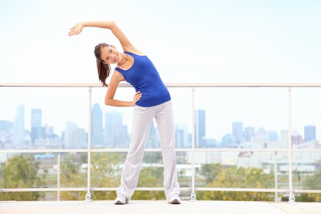 City workout woman stretching after running exercise with skyline in background  Young fitness model training  Mixed race Asian Chinese   Cauasian young woman in Montreal, Quebec, Canada  Stock Photo