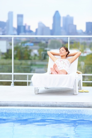 lounger: Woman relaxing at rooftop pool in city with skyline in background  Young female model lying down at sun lounger with Montreal skyline in background