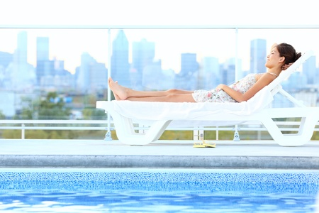 rooftop: Urban luxury city lifestyle woman lying by pool relaxing in sun lounger during summer in Montreal, Quebec, Canada