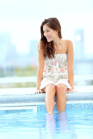 swim race: Pool woman relaxing sitting in summer dress with legs in pool smiling happy with skyline in background  Beautiful mixed race Asian Chinese   Caucasian girl  Stock Photo
