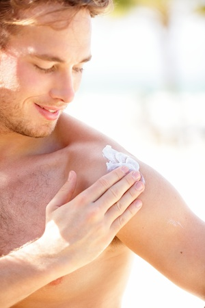 Sunscreen. Man putting sun screen  sun block on shoulder on sunny summer day during vacation on beach resort. Young handsome Caucasian male model smiling happy.