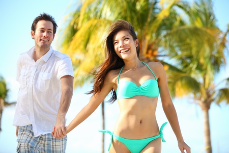 Couple having fun on beach. Happy young interracial couple running on beach during summer vacation on tropical resort. Asian woman, Caucasian man smiling happy in Varadero, Cuba photo