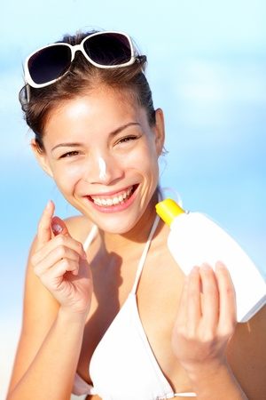 Vacation woman putting sunscreen on nose on beach. Cute beautiful young woman on summer holiday enjoying the sun on sunny summer day. Multiracial Asian  Caucasian girl. photo
