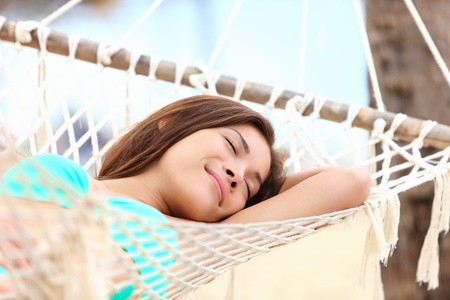 Vacation woman lying in hammock relaxing and sleeping smiling happy during summer holidays in tropical resort. Mixed race Asian  Caucasian girl in bikini. photo