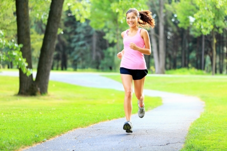 Running woman in park in summer training. Asian sport fitness model in sporty running clothes. photo