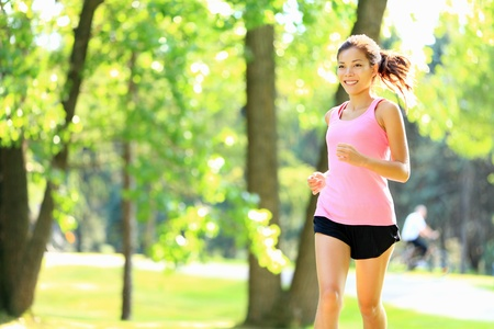 jogging in park: Runner - woman running in city park on sunny summer day with with sunshine in green trees. Asian  Caucasian fitness sports model during outdoor workout.
