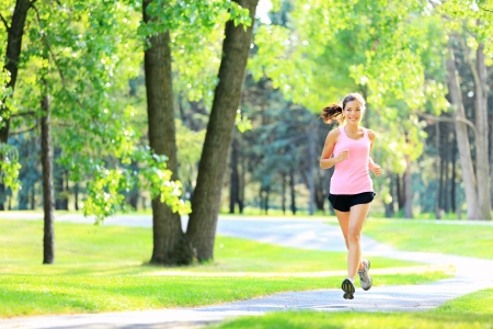 Jogging woman running in park in sunshine on beautiful summer day. Sport fitness model of mixed Asian  Caucasian ethnicity training outdoor for marathon.