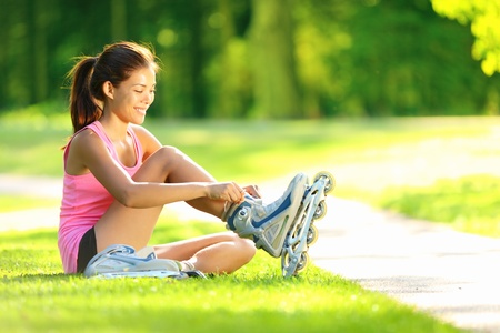 Woman skating in park. Girl going rollerblading sitting in grass putting on inline skates. Mixed race Asian Chinese  Caucasian woman in outdoor activities. Stock Photo