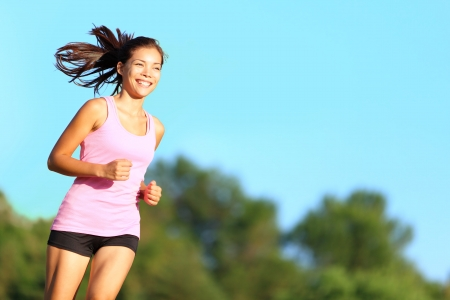 Happy woman running in city park. Asian girl runner jogging smiling aspirational outside on beautiful summer day. Mixed race Asian Chinese / Caucasian female fitness sport model training outdoors. 스톡 콘텐츠