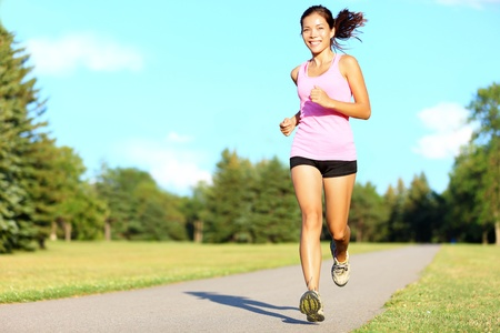 Sport fitness woman running in park on summer day. Asian female runner during outdoor workout. Fit sport fitness model of mixed Asian  Caucasian ethnicity. photo