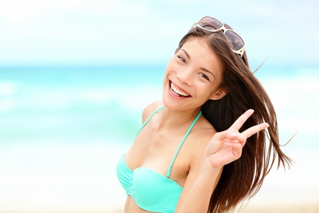 Happy beach vacation woman joyful smiling on beautiful tropical beach during summer holidays. Fresh mixed race Caucasian / Chinese Asian bikini model. photo