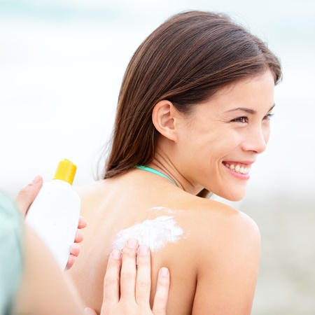 Sunscreen lotion on beach. Couple applying sunscreen lotion. Woman smiling happy on summer vacation. Mixed race Caucasian  Asian Chinese young woman. photo