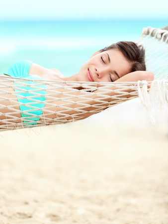 Vacation woman relaxing on beach in hammock on summer holidays resort. Beautiful happy multiracial Asian Chinese / Caucasian young woman. photo