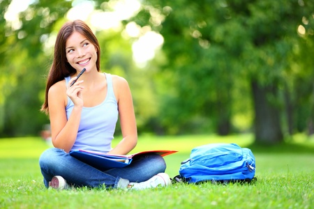 student reading: Student thinking looking in park Joyful happy asian girl student sitting writing and reading outside on university campus or park. Mixed race Chinese Asian  Caucasian female student woman looking at camera.