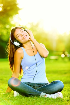 listen to music: Woman listening to music. Female student girl outside in park listening to music on headphones while studying. Happy young university student of mixed Asian and Caucasian ethnicity.