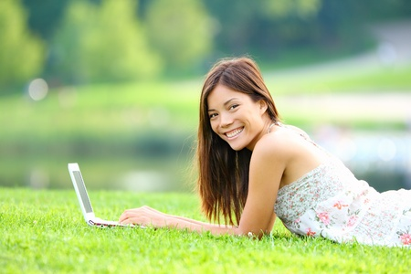 Girl in park on laptop  College student studying on laptop in summer or spring city park  Beautiful happy mixed race Caucasian   Asian chinese university student lying in the grass outside  photo