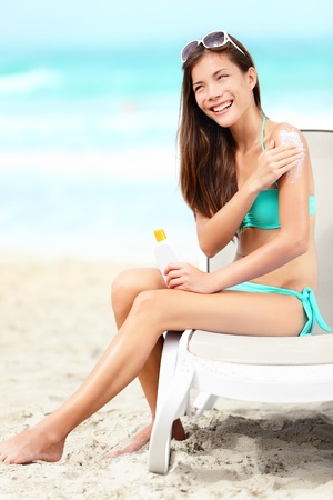 sun lotion: Suntan lotion - woman applying sunscreen smiling happy in bikini on beautiful beach during summer vacation on holiday resort  Pretty mixed race Asian Chinese   Caucasian female model in bikini sitting on sunbed