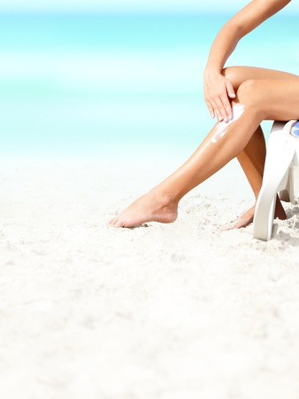 sunblock: Suntan lotion   sunscreen  Woman applying sunblock cream on leg on beautiful tropical beach with white sand on summer vacation
