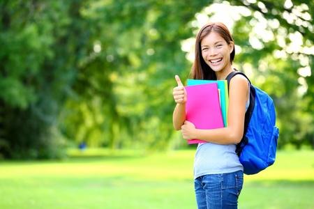 Student w parku pokazując szczęśliwe kciuki znak mieszany sukces rasy kaukaskiej kobiety azjatyckie Student sprawującego książek poza