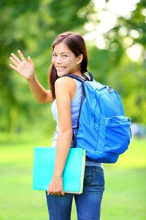 Woman student waving hello walking with school back in park smiling happy  Young female college or university student of mixed Asian   Caucasian race outside  photo
