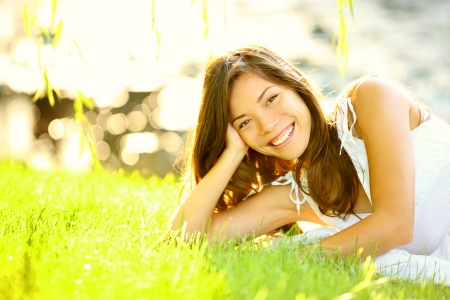 woman smiling: Summer girl in grass smiling happy. Lifestyle image of beautiful young woman in summer dress lying joyful in park on sunny sunshine day. Mixed race Caucasian  Asian Chinese female model.
