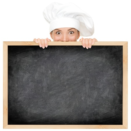 asian cook: Chef showing restaurant menu blackboard - empty blank with copy space for text etc. Funny woman cook peeking over sign. Beautiful happy smiling mixed race Caucasian  Asian female model. Isolated on white background. Stock Photo