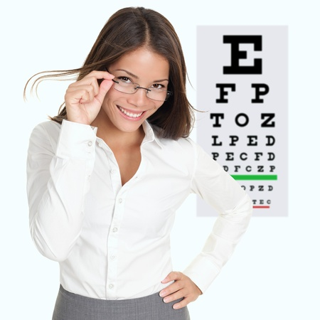 Optician or optometrist showing Snellen eye exam chart wearing eye wear glasses. Female mixed race Caucasian  Asian Chinese model