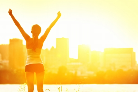 arms up: Success winner woman standing with arms up joyful after outdoors workout. Half silhouette on sunny warm summer day with city skyline in background, From Montreal, Quebec, Canada. Stock Photo