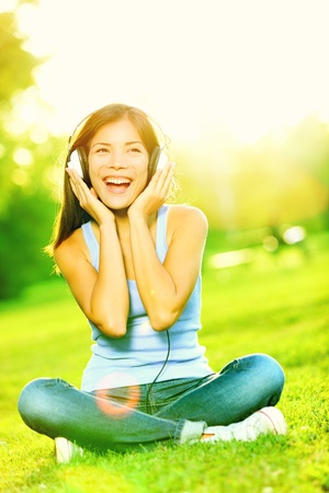 Music headphones woman in park singing listening to music on smart phone or mp3 player in sunshine in park. Mixed race Asian  Caucasian girl smiling happy. photo