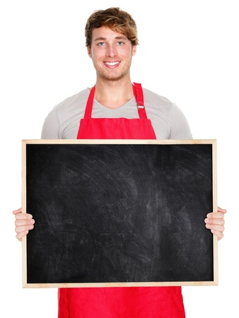 shop owner: Small business owner showing blank empty blackboard sign wearing apron. Handsome young shop owner man isolated on white background smiling happy. Stock Photo