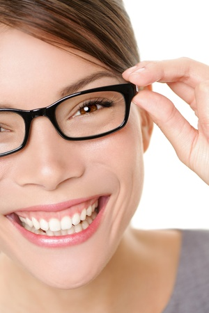 eye wear: Glasses woman showing eyewear smiling happy holding glasses frame  Closeup of young multiethnic mixed race asian caucasian woman smiling  White background