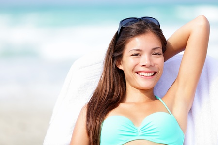 beautiful armpit: Vacation woman relaxing on sunbed on beach in bikini smiling happy looking at camera  Beautiful young multiracial Caucasian   Asian Chinese enjoying summer holidays in the sun  Stock Photo