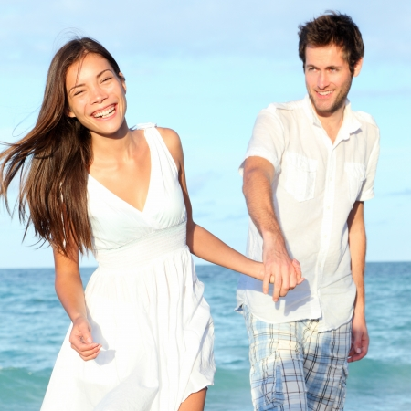 interracial relationships: Beach couple walking happy, carefree and joyful on summer vacation  Interracial young couple holding hands  Asian woman, Caucasian man  From Varadero Beach, Cuba  Stock Photo