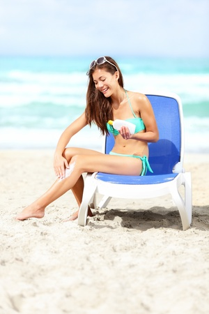varadero: Woman on beach applying sunscreen lotion   sun block on legs smiling happy sitting in bikini on sunbed tanning during sunny summer vacation on Varadero Beach, Cuba