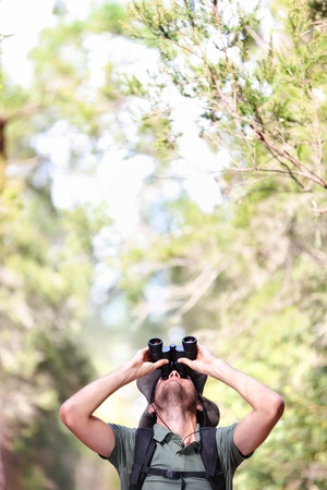 Binoculars - man hiker looking up at copy space during outdoors hiking trip