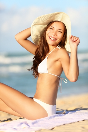 Happy beach vacation woman on summer holidays holding summer hat smiling in joyful bliss  Beautiful young mixed race Asian Chinese   Caucasian model in bikini  photo