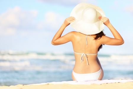 tanning: Summer vacation woman sitting on beach holding beach hat enjoying summer holidays looking at the ocean  Beautiful back side of model in bikini sitting down  Stock Photo