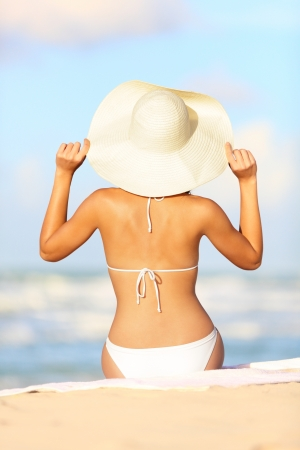 tanning: Travel vacation woman on summer holiday on beach holding her summer hat sitting in the sand enjoying ocean  Back view of beautiful girl in white bikini