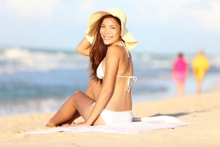 Vacation beach woman happy  Beautiful girl in bikini smiling in blissful joy at camera while sitting on beach during summer holidays travel  Pretty multiracial Caucasian   Asian Chinese model in bikini  photo