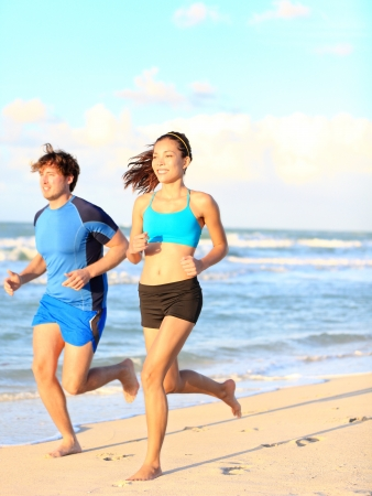 Sport couple running on beach during outdoor fitness exercise   Asian woman and caucasian man runners  photo