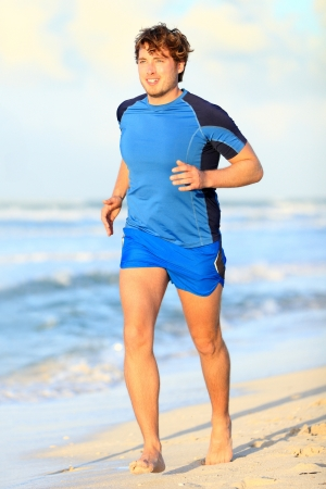 Running man  Male runner jogging on beach barefoot during outdoor sport fitness exercise  Caucasian male fitness model in his twenties photo