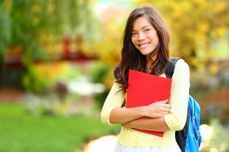 student: Beautiful woman holding red book in autumn background. Asian student girl on campus