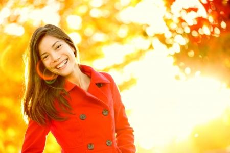 Autumn fashion girl wearing red trench coat in sun flare foliage. Fall woman portrait of happy lovely and beautiful mixed race Asian Caucasian young woman in forest in fall colors. photo