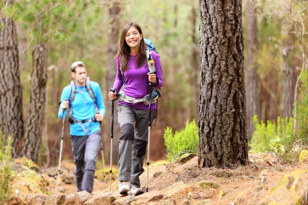 trekking pole: Hikers in forest. Couple hiking in fall forest. Asian woman hiker in front smiling happy. Photo from Aguamansa, Orotava, Tenerife, Canary Islands, Spain. Stock Photo